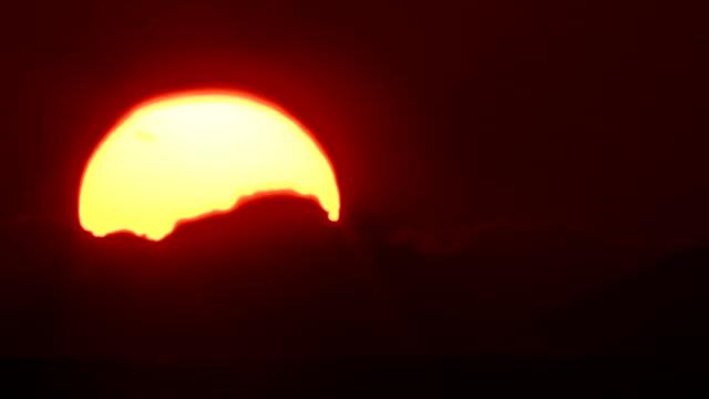 cu t/l sun setting behind clouds - 沈没する点の映像素材/bロール