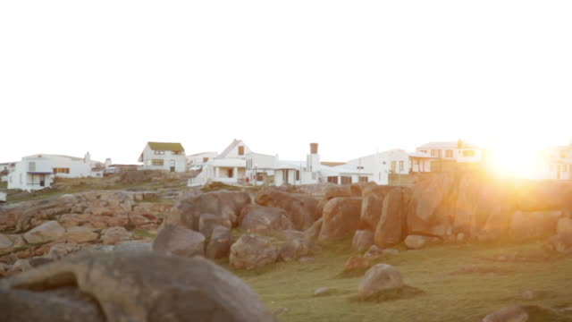 vídeos de stock, filmes e b-roll de sun setting behind coastal homes, cabo polonio, rocha department, uruguay - uruguai