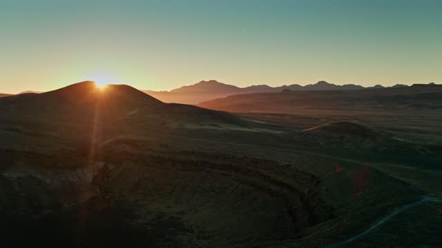 sun setting behind hill in lunar crater national natural landmark - aerial - natural landmark stock videos & royalty-free footage