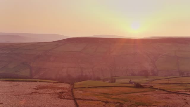 sun setting behind hill in west yorkshire pennines - drone shot - lancashire stock videos and b-roll footage