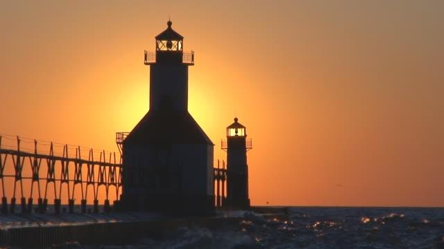 vídeos de stock, filmes e b-roll de sol se pondo atrás farol parte 11 - lago michigan