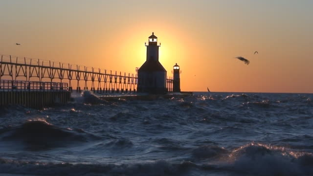 sun setting behind lighthouse part 8 - michigan stock videos & royalty-free footage