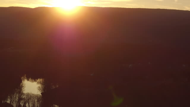 sun setting behind mountain over a bendy river on a winter day in new york - contea di ulster stato di new york video stock e b–roll