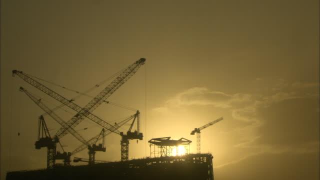 ws la sun setting behind multiple cranes sitting atop building under construction, guilin, guangxi zhuang autonomous region, china - guangxi zhuang autonomous region china stock videos & royalty-free footage