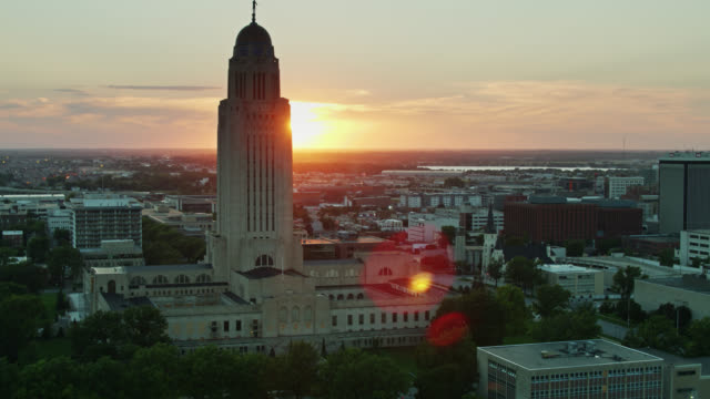 sun setting behind nebraska state capitol - aerial - nebraska stock videos & royalty-free footage