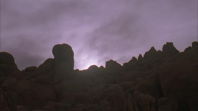 ws, sun setting behind rocks / california - palm springs california stock videos & royalty-free footage