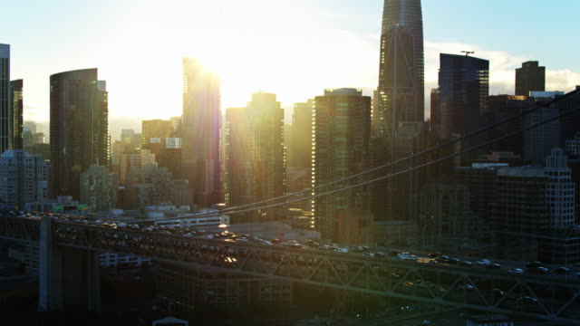 sun setting behind the bay bridge and the san francisco financial district - oakland california stock videos & royalty-free footage