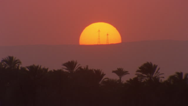 ha tl ws sun setting behind two power towers with palm trees in foreground/ egypt - palm tree stock videos & royalty-free footage
