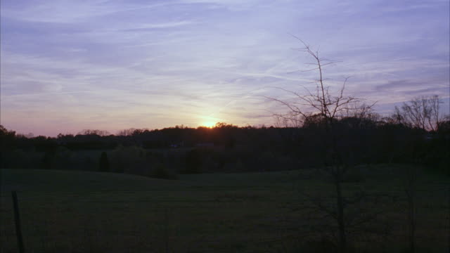 WS Sun setting behind wooded area and sprawling green meadow / Newnan, Georgia, United States