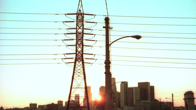stockvideo's en b-roll-footage met handheld sun setting beyond a street lamp light standing in the middle of street in industrial area, with unnatural tinting / los angeles, california, united states - cross processen