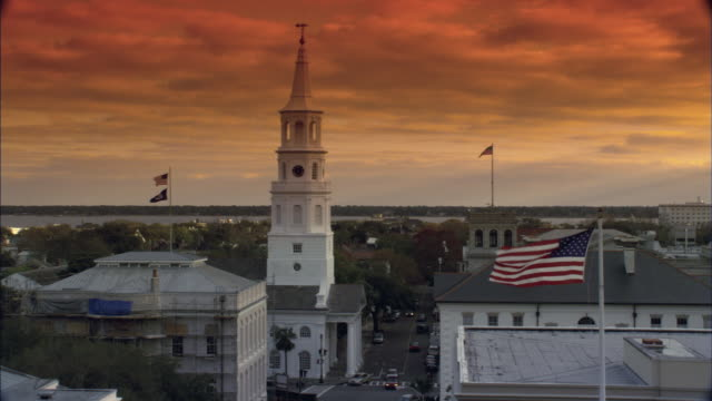 zi sun setting beyond american flags raised on poles and st michael's steeple / charleston, south carolina, united states - south carolina stock videos & royalty-free footage