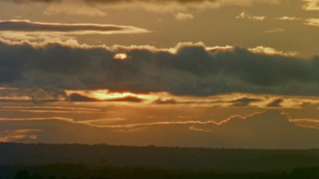 vídeos de stock e filmes b-roll de 1957 montage sun setting in clouds and waves splashing ashore on rocks / cornwall, england - 1957
