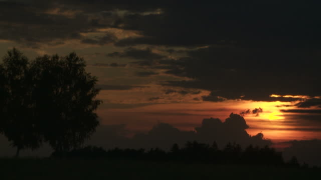 t/l sun setting in cloudy sky - dämmerung stock videos & royalty-free footage