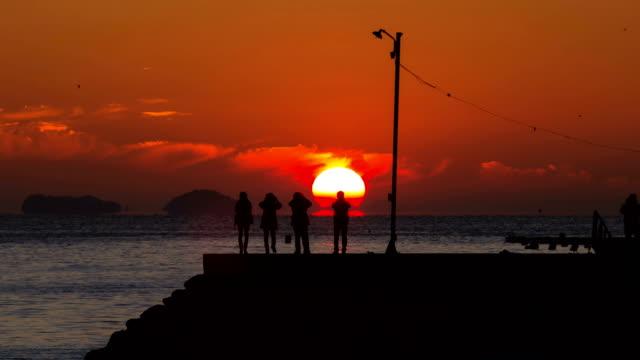 sun setting off the ocean with omega shape reflection in dala village / tongyeong, gyeongsangnam-do, south korea - omega sun mirage stock videos & royalty-free footage
