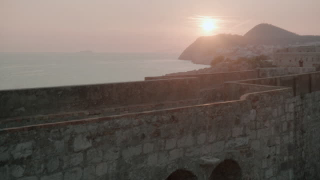 ws sun setting on the horizon over mountains and an ancient building - formato panoramico con bande nere video stock e b–roll