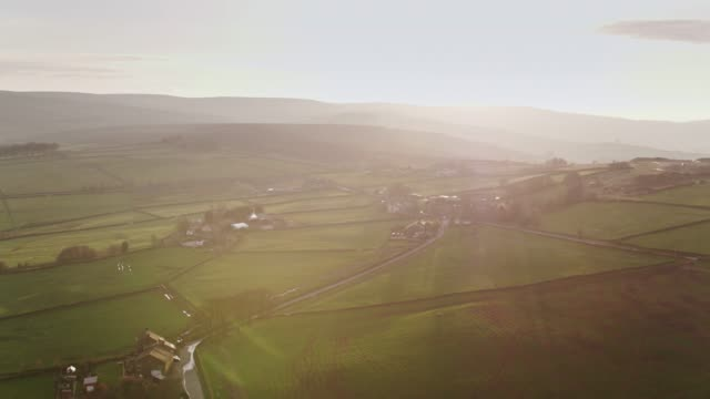 sun setting over english countryside - aerial view - scena rurale video stock e b–roll