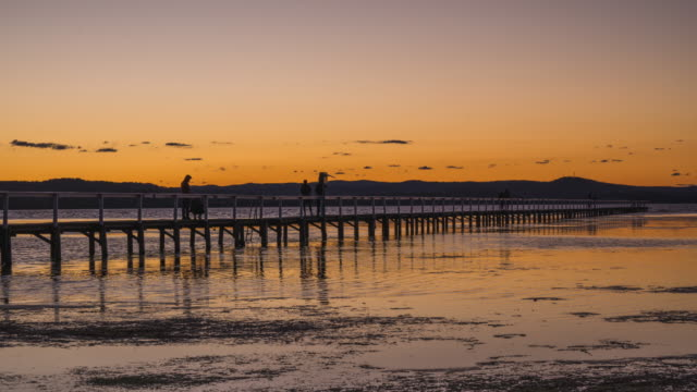 sun setting over lake in new south wales. - jetty stock videos & royalty-free footage