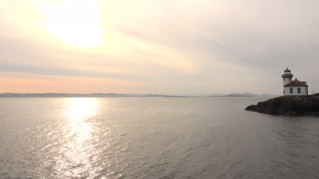 Sun Setting Over Large Lake with Lighthouse on Coastline