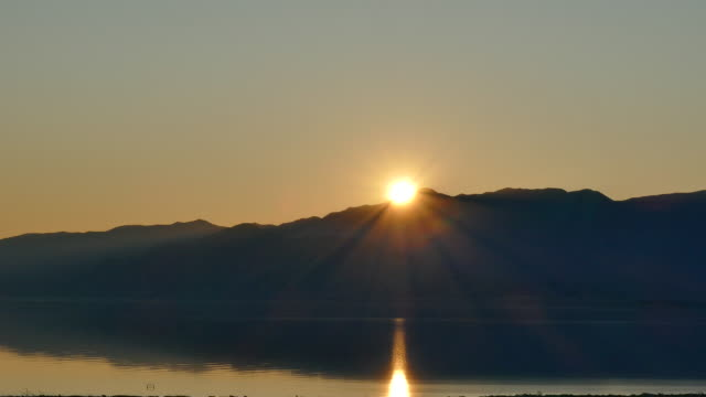 4k sun setting over mountains golden sunlight reflecting in rippling water - san andreas fault stock videos & royalty-free footage