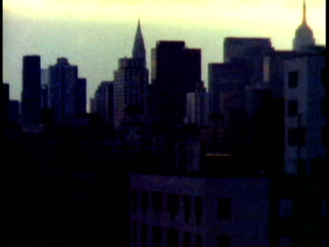 1972 montage t/l sun setting over skyline of midtown manhattan / zi various building rooftops / new york city - st. patrick's cathedral manhattan stock videos and b-roll footage