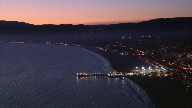 AERIAL Sun setting over the pier and amusement park, with the mountains beyond / Santa Monica, California, United States