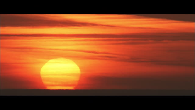 ws sun setting over the sea, a golden disc in a red sky - 50 seconds or greater stock videos & royalty-free footage