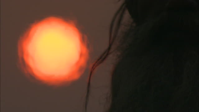 A sun shimmers in the heat of a cremation ceremony where a bearded man stands watch.