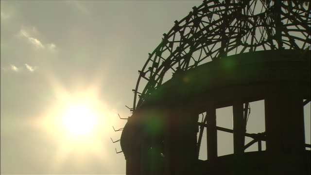 sun shines above silhouetted hiroshima peace memorial (genbaku dome - 1945 hiroshima blast came through the roof and dome's metal frame remained to become symbol of the bombing) - 1945 stock videos and b-roll footage