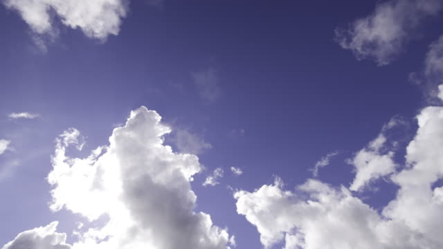 vídeos y material grabado en eventos de stock de sun shines behind billowing cumulus clouds in blue skyue sky and behind clouds - sólo cielo