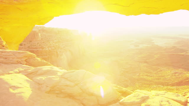 Sun shines in Arches National Park over canyon