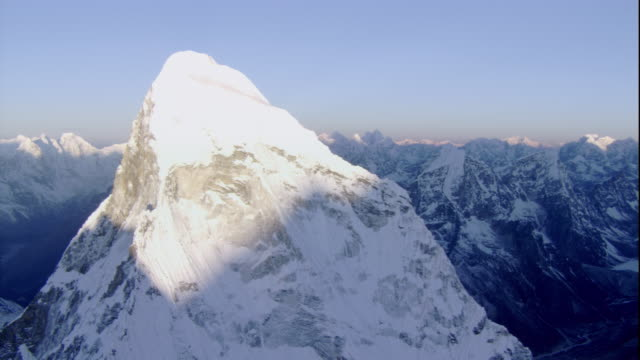 Sun shines on a snow-covered mountain peak in the Himalayas. Available in HD.