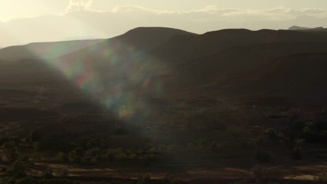 sun shines on buildings in ounila valley, morocco - lehm mineral stock-videos und b-roll-filmmaterial