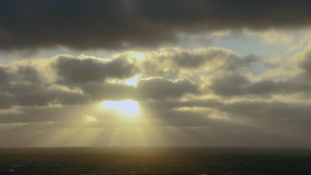 vidéos et rushes de sun shines through clouds over sea - phénomène naturel