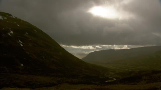 Sun shines through rain clouds over valley, Cairngorms, Scotland