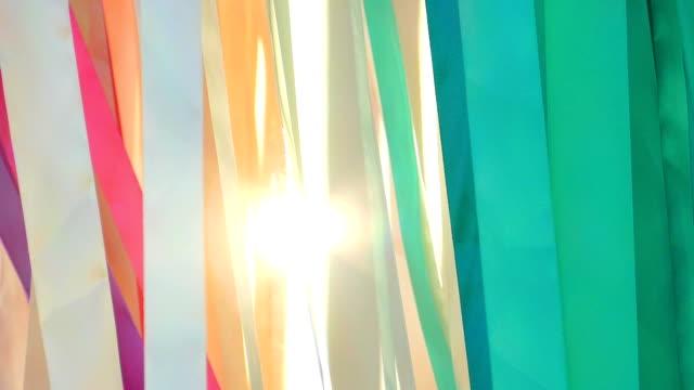 vídeos de stock, filmes e b-roll de sol brilha através de fitas coloridas (câmera lenta) - material têxtil