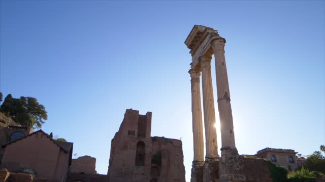 Sun shines through the three columns at the Temple of Castor and Pollux at the Roman Forum in Rome, Italy