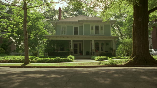 stockvideo's en b-roll-footage met sun shines through the trees on a two-story suburban house. - gevel