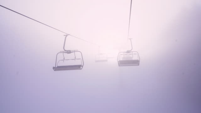 4k sun shining behind ski lift chairs moving along wire in fog, real time - inquadratura dalla sciovia video stock e b–roll
