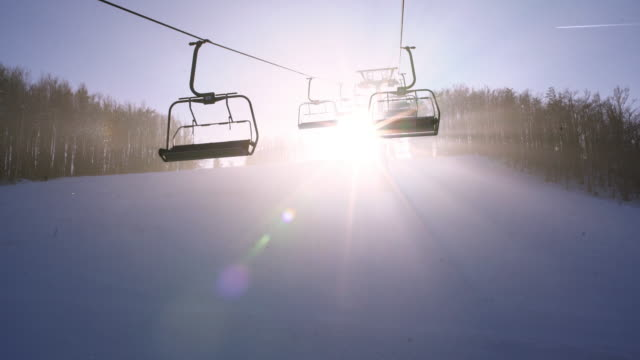4k sun shining behind ski lift chairs moving along wire in fog, real time - stazione sciistica video stock e b–roll