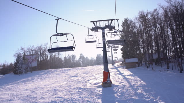 4K Sun shining behind ski lift chairs moving along wire in fog, real time