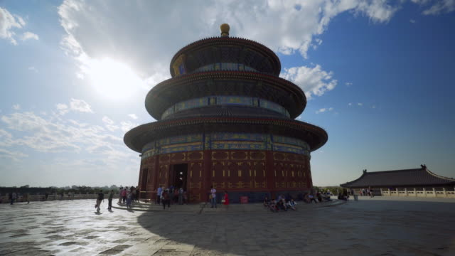 vidéos et rushes de sun shining on chinese temple of heaven structure with tourists on footpath - beijing, china - temple du ciel