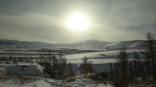 WS Sun shining over snowy landscape / Inner Mongolia, China