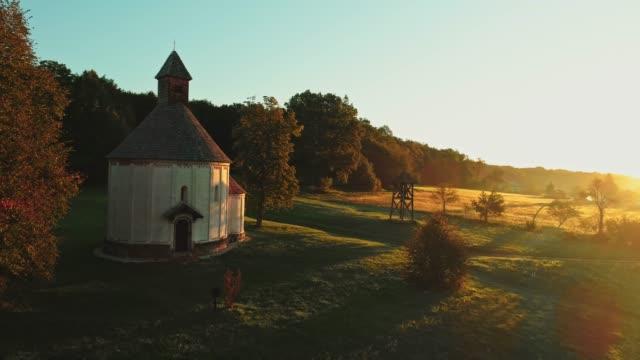 ms sun shining over tranquil,idyllic rural landscape and round church,prekmurje,slovenia - prekmurje stock videos & royalty-free footage