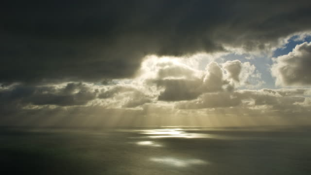 t/l, ws, sun shining through heavy clouds above ocean, auckland, new zealand - 太陽光線点の映像素材/bロール