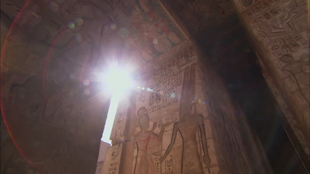 t/l ms la sun shining through medinet habu temple (mortuary temple of ramesses iii) columns decorated with hieroglyphics / medinet habu, luxor governorate, egypt - egypt stock videos & royalty-free footage