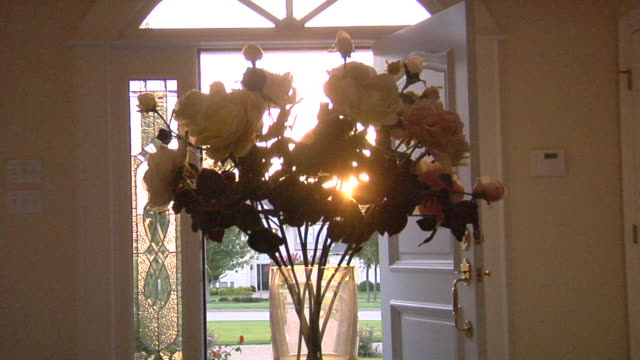 MS ZI Sun shining through roses in vase on table in front of open front door of suburban home/ Temple, Texas