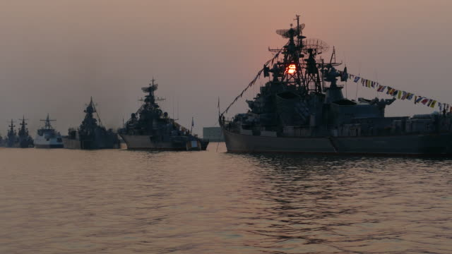 sun silhouettes warships at sunset