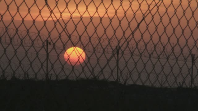 sun through barbed wire and fence at sunset - chainlink fence stock videos and b-roll footage