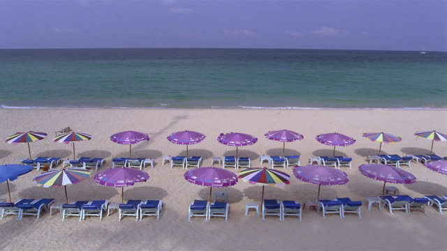 MS, HA, Sun umbrellas and empty beach chairs facing ocean on Kata-Noi Beach, Phuket, Thailand