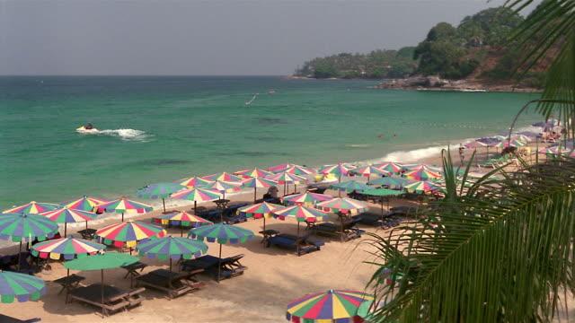 ms, ha, sun umbrellas and empty beach chairs facing ocean on kata-noi beach, phuket, thailand - solfjäderspalm bildbanksvideor och videomaterial från bakom kulisserna